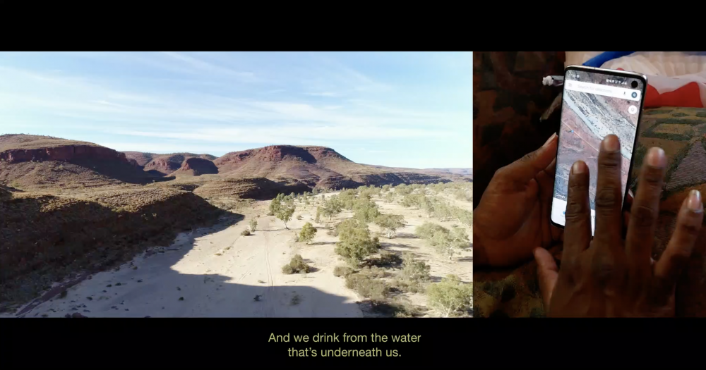 """Video Still, *INFRACTIONS*, 2019, 1:03:00, HD video, split screen with text, Dolby 5.1  Que Kenny (Western Arrarnta) shows an unlined evaporation pond near gas infrastructure and dried up sacred springs in Ntaria (Hermannsburg). The landscapes of Namatjira's paintings are now connected by a pipeline to the Queensland export market.  *""""Because we have a conventional mining company there already, that's getting conventional gas, for sure there are other resources they want to get their hands on. It's a threat to us, we're not benefitting from it.""""*"""