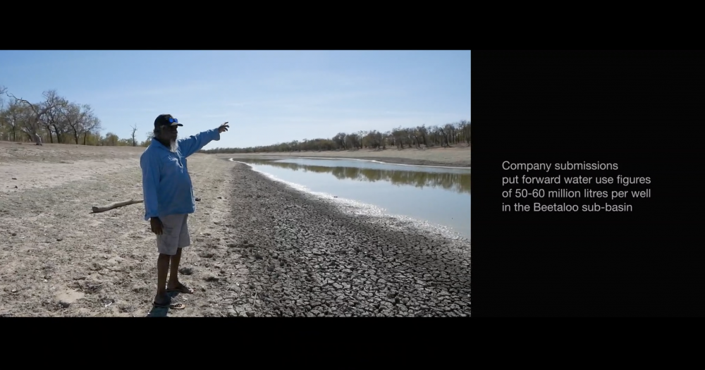 """Video Still, *INFRACTIONS*, 2019, 1:03:00, HD video, split screen with text, Dolby 5.1  Artist and former water bore runner Dimakarri 'Ray' Dixon (Mudburra), points to existing and prospective wells upstream of Lake Woods and Newcastle Waters, an important gathering ground, historic also for 1966 pastoral industry walkoffs.  *""""It's a Native Title area, which is another way of saying, nothing much we can do. But there is time. There is a thing we can do. Get everyone together, and stand*"""